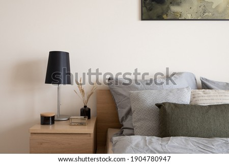 Comfortable bed with stylish, wooden bedside table with black lamp, black vase with decorative grass, fancy black container and glass jewelry box