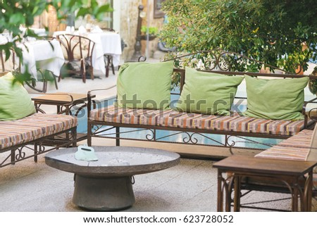 Comfortable Bench With Green Cushions And A Round Table In The Courtyard  Cafe