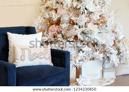 Comfortable blue sofa chair next to a beautifully decorated white Christmas tree. Noel cushion on seat and wrapped presents under the tree.