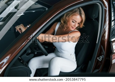 Comfortable car. Woman in formal clothes is indoors in the autosalon.
