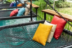 Comfortable colorful pillows lay on rope netting in garden for resting and relaxation.