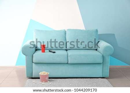 Comfortable couch with popcorn and drink indoors. Home cinema #1044209170
