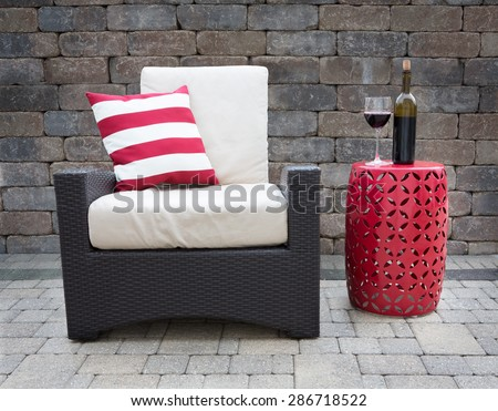 Comfortable Dark Wicker Patio Chair Outfitted with Plush Cushions Beside Modern Red Table with Bottle and Glass of Red Wine on Outdoor Stone Affluent Patio