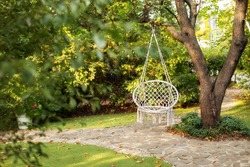 Comfortable hanging wicker white chair in summer garden. Cozy hygge place for weekend relax in garden. Hammock chair in boho style hanging on tree. Cozy exterior backyard. Concept of rest outdoor.