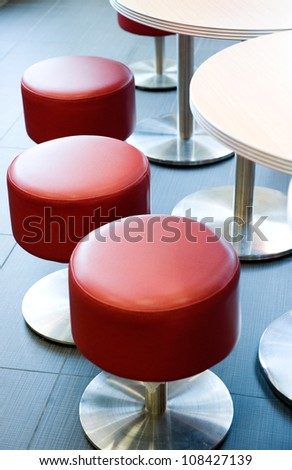 Comfortable leather-and-wood stools in a restaurant / bar.