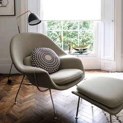 Comfortable light green armchair in cosy setting with cushion on dark wood floor in front of tall window.
