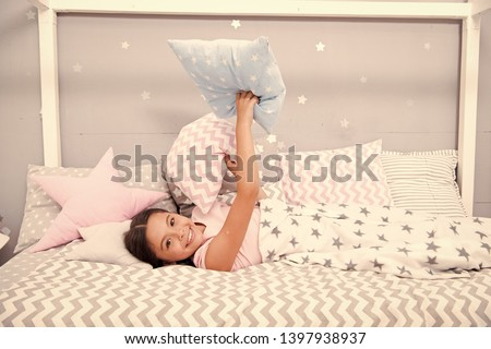Comfortable pillow. Girl smiling child lay bed star pattern pillows and plaid bedroom. Bedclothes for children. Girl kid waking up morning. Modern fashionable bedclothes. Comfortable place for rest.