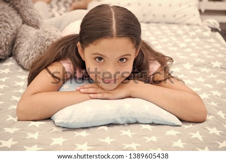 Comfortable pillow. Girl smiling happy child lay on bed with star pattern pillows and cute plaid in her bedroom. Bedclothes for children. Girl kid waking up in morning. Modern fashionable bedclothes.