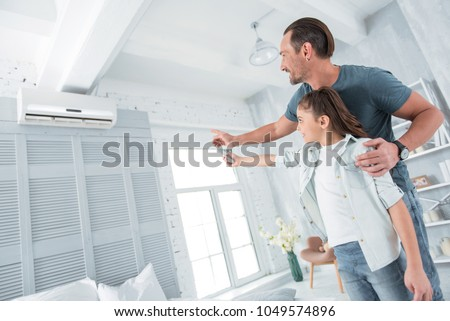 Comfortable temperature. Positive happy joyful man standing near his daughter and pointing at the air conditioner while teaching her how to use it #1049574896