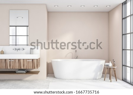 Comfortable white bathtub and sink with vertical mirror standing in stylish bathroom with beige walls and concrete floor. 3d rendering