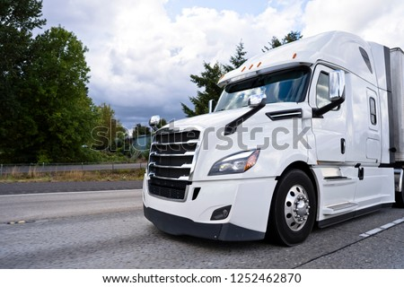 Comfortable white modern bonnet big stylish professional rig semi truck running on divided highway with dry van semi trailer for delivery commercial cargo to point of destination #1252462870