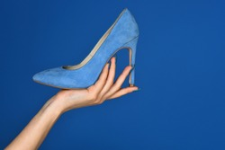 Comfortable women shoe in gentle lady's hand on blue background. Concept of advertising shoes which are on sale. Women's high heels with a discount. Cinderella's dream shoes in shop