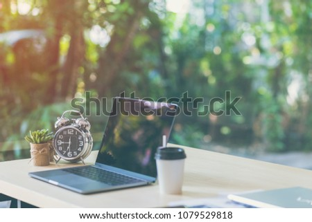 Comfortable workplace, Office desk with blank screen laptop and clock, plant, Nature light bokeh background. Startup at work in the morning, coffee shop, Co working space. Copy space, Vintage