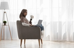 Comfortable workplace, rest in comfort, lazy, watch video, film. Happy millennial arab lady in hijab with laptop sit in armchair in minimalist living room, drinking tea on window background, profile