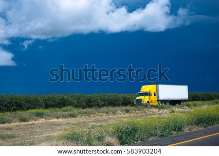Comfortable yellow semi truck for long haul going with a cargo in dry van trailer carrying out flight on timely delivery to the customer by road passing in the middle of the California orchard plains #583903204
