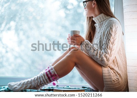 Comforting cozy woman in knitted winter socks and white warm sweater resting and warming up with a cup of hot cocoa on a window sill by the window at home in winter time. Cozy time  #1520211266