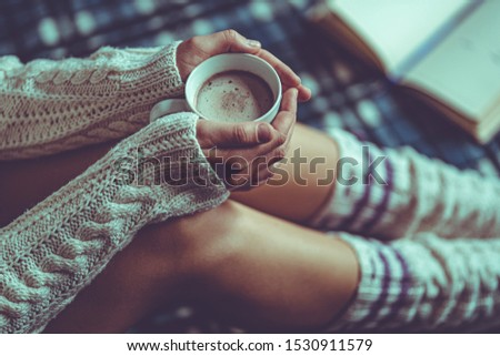 Comforting cozy woman in knitted winter socks and white warm sweater sitting on a plaid blanket and warming up with a cup of hot cocoa at home in winter time. Cozy time and winter drinks  #1530911579