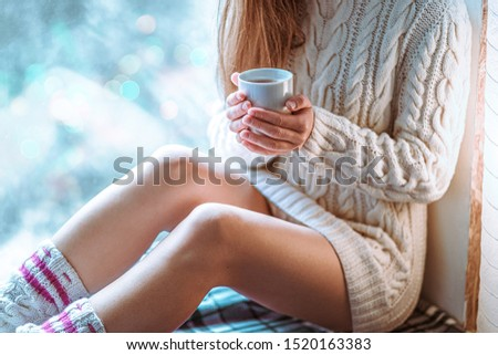Comforting cozy woman in knitted winter white warm sweater resting and warming up with a cup of hot cocoa on a window sill by the window at home in winter time. Cozy time