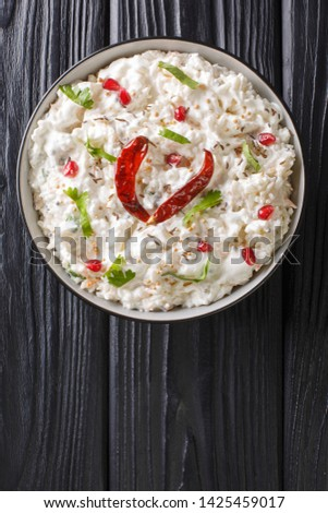 Comforting Curd Rice is a popular dish from South India with yogurt and then tempered with spices closeup in a plate on the table. Vertical top view from above Stok fotoğraf ©