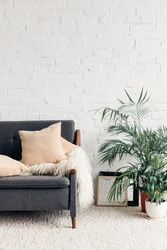 comfy couch with flowerpots in white living room interior with brick wall, mockup concept