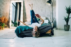 Comfy loft design interior in flat apartment, portrait of successful female reader holding bestseller book in hand and laughing feeling happiness from own life, cheerful woman lying on bed in home