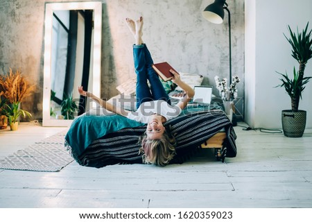 Comfy loft design interior in flat apartment, portrait of successful female reader holding bestseller book in hand and laughing feeling happiness from own life, cheerful woman lying on bed in home Сток-фото ©