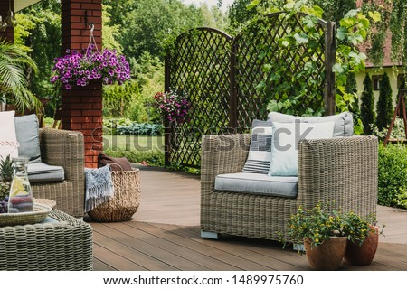 Comfy wicker armchair with pillows on wooden terrace of trendy suburban home