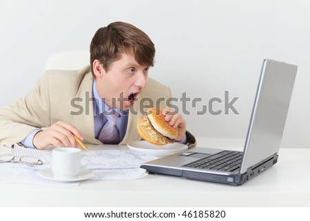 Comic clerk eats a sandwich looking at the screen
