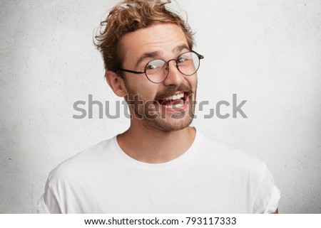 Comic funny young male with happy expression express positive emotions, glad to be praised by someone, look happily through spectacles, isolated over white background. Facial expressions concept #793117333
