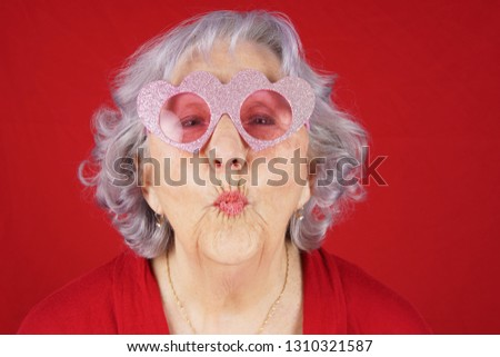 Comical granny with heart shape glasses blowing kiss