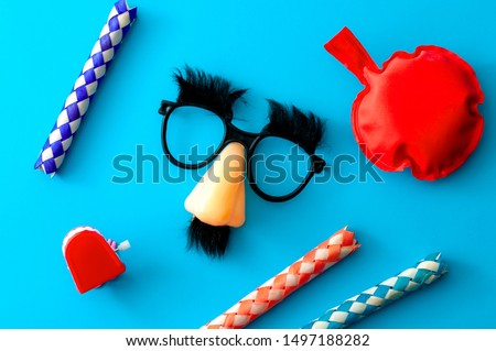 Comical prank, April fools practical joke and goofy disguise concept farting bag, chattering teeth, chinese finger trap and novelty glasses with fake nose and eyebrows isolated on blue background Foto stock ©