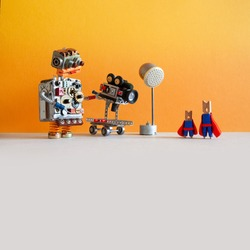 Comical robotic toy cameraman makes a happy ending movie about super heroes. Funny clothespin actors, robotic operator, camcorder spotlight. Yellow orange wall, gray floor background, empty space