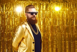 Comically serious cool bearded man in sunglasses stands on a golden background. Fat red man in an extravagant golden jacket and with a massive chain around his neck. Stylized party concept.