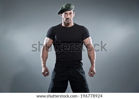 Commander muscled action hero man wearing black t-shirt and pants. Studio shot against grey.