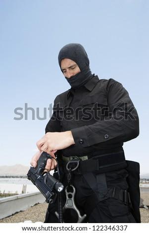 Commando preparing his handgun on military training