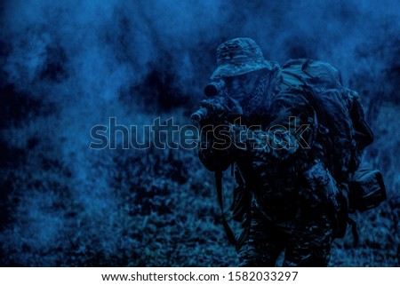 Commando soldier, army special operations fighter, elite troops sniper in camo uniform, carrying tactical backpack, aiming weapon, shooting from rifle, watching through optical sight at night mission