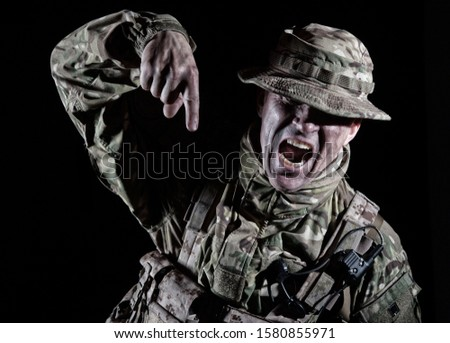 Commando soldier, elite forces fighter, special operations troops infantry in camo uniform, pointing finger down, yelling with anger, screaming order, showing attention direction, low key portrait