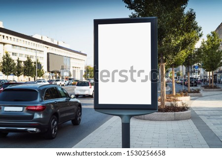 Commecrial space in pedestrian area for advertising products and services of business owners. Drivers passing by billboard see ads from marketing campaigns of firms and companies. Busy traffic in city