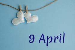 Commemorative date April 9 on blue background with white hearts with clothespins, flat lay. Holiday calendar concept