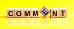Comment word written on wood block. Comment text on table, concept. Word Comment is made of wooden building blocks lying on the table and on a light yellow background.