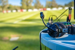 commentator headsets on the table next to the football field. stream for television and radio