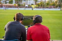 commentators on football game watching match. stream for television and radio