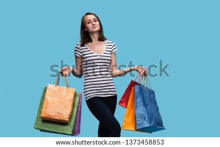 Commerce and shopping season. Happy young woman with paper shopping bags.