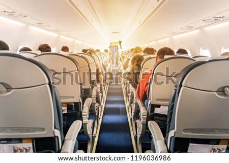 Commercial aircraft cabin with rows of seats down the aisle. morning light in the salon of the airliner. economy class