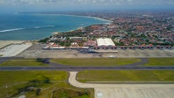 Commercial aircraft taxi on the runway at Denpasar Airport in Bali, Indonesia. Drone view of a big jet preparing to take off. Jet airplane turns to runway. Passenger jet prepares for departure.