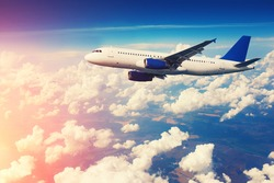 Commercial airliner flying above clouds with blue sky in background. Vintage toning, sun flare