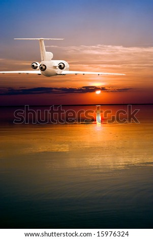 Commercial airliner flying over water to sun