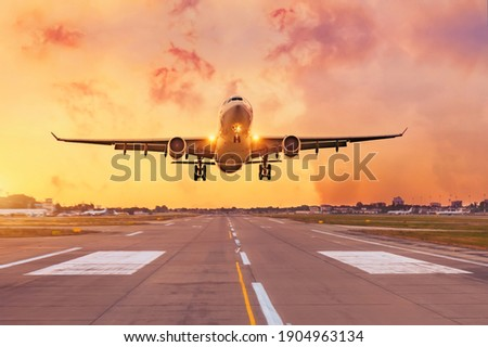 Commercial airliner passenger plane fly down over landing at sunset Photo stock ©