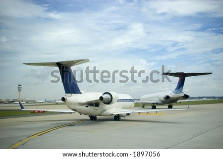 Commercial airliners at a busy airport under a blue sky