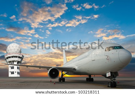 Commercial airplane at the airport with control tower